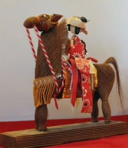 A woman, perhaps a bride, constructed of paper, rides a horse woven of some fine woody material, and decorated with silk cords and glass-headed pins.