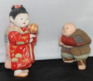 Two kimekomi dolls. The one on the right is older, probably 19th-century.  The one on the right is a typical mid-20th c. representation of a child playing. it is about 4 inches tall.
