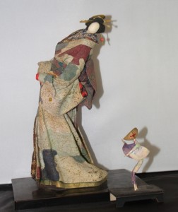 A 12-inch-tall modern doll of washi paper, and beside it a tiny paper doll depicting awa odori, the rice-planting dance.