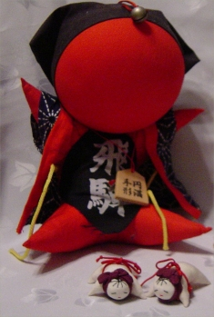 "Hoko shapes: A modern ""monkey"" or sarubobo, sold as a good-luck doll, and two small cloth"
